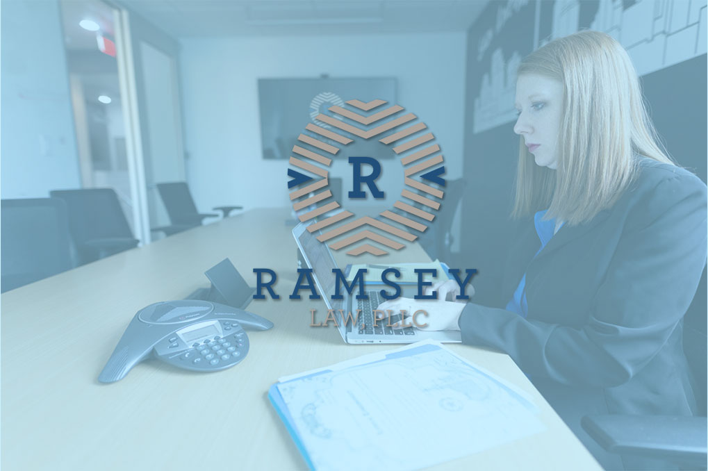 Ramsey Law logo over Amber Ramsey working on her laptop at conference table