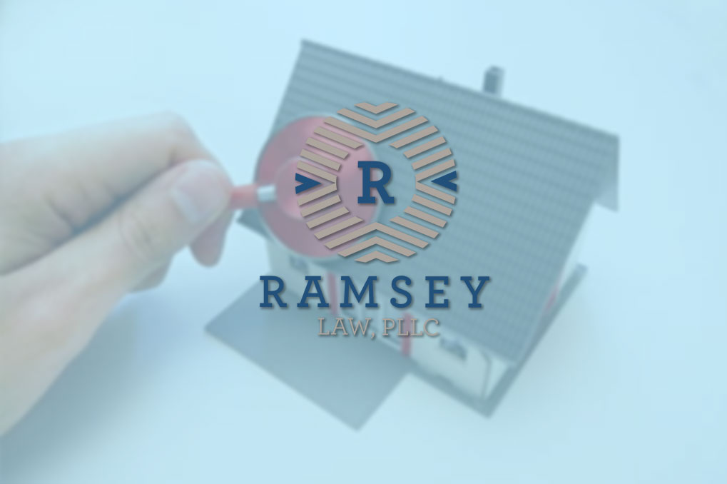 Ramsey Law logo over hand pointing to toy house