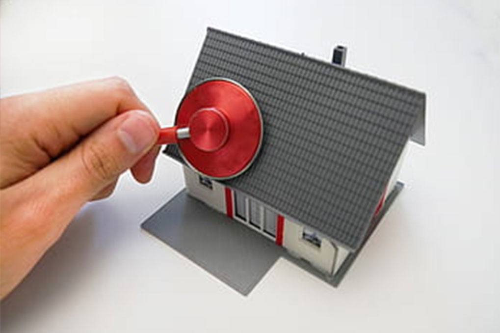 hand holding red stethoscope against toy house